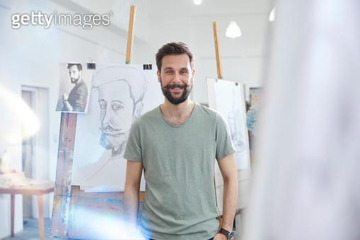 Portrait smiling, confident male artist sketching in art class studio - gettyimageskorea