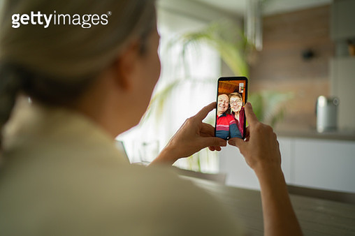 smiling senior adult parents talking with daughter over mobile phone video call - gettyimageskorea