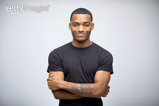 Portrait of confident young man with arms crossed standing. Tattooed male is wearing black t-shirt. He is smiling against white background. - gettyimageskorea