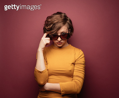 Young woman wearing gold shirt on red background - gettyimageskorea