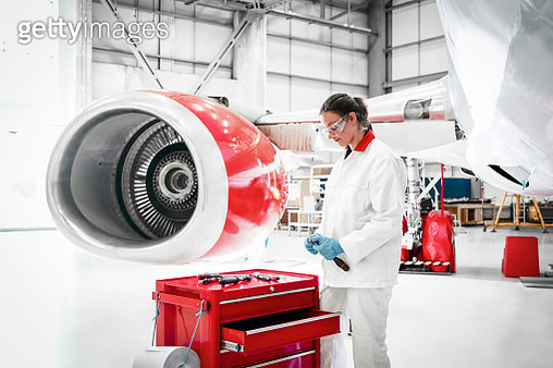 Woman holding tools by airplane engine by hangar - gettyimageskorea
