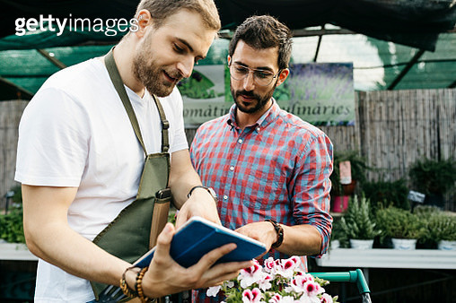 Worker with tablet in a garden center advising customer - gettyimageskorea