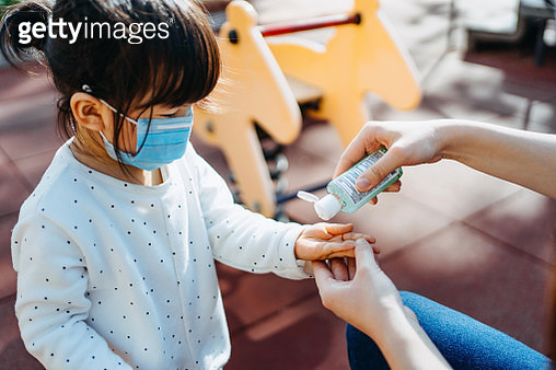 Young mother squeezing hand sanitizer onto little daughter's hand in the playground to prevent the spread of viruses - gettyimageskorea