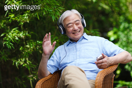 An elderly man was sitting in a chair with headphones - gettyimageskorea