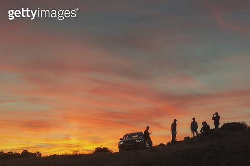 Silhouette of group of friends near car at sunset in natural setting - gettyimageskorea