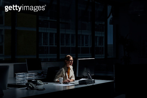 Businesswoman using computer in dark office - gettyimageskorea