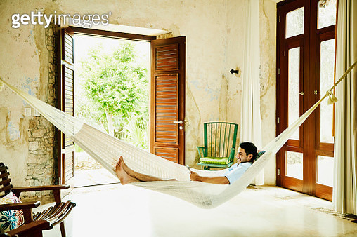 Smiling man relaxing in hammock in room at luxury resort reading digital tablet - gettyimageskorea