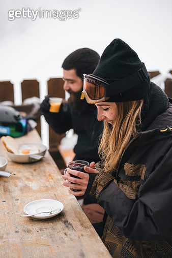 Couple in skiwear having a hot drink at mountain lodge - gettyimageskorea