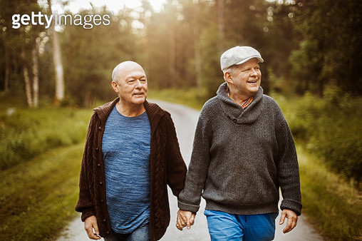 Happy gay couple looking away while walking on road amidst trees - gettyimageskorea