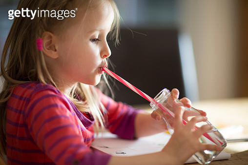CHild (6-7) sitting at a table drinking water through a reusable straw in a glass bottle - gettyimageskorea