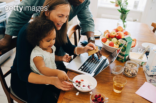 Parents shopping online on laptop while looking at daughter having breakfast in dining room - gettyimageskorea