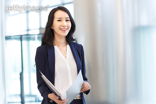 Successful business woman holding a folder - gettyimageskorea