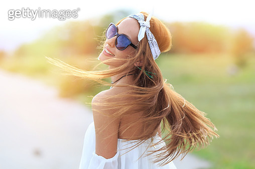 Young smilling woman posing on the road. Wears white blouse, headband and sunglasses, flowing hair. Focus on foreground. - gettyimageskorea