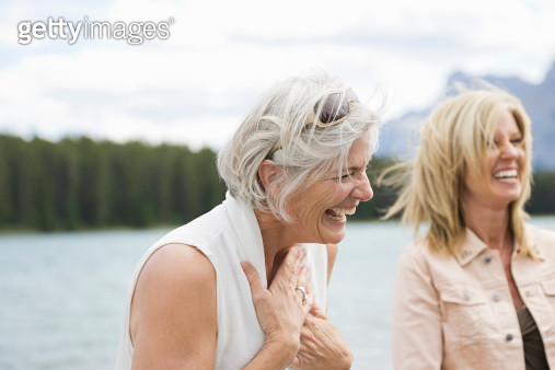 Mature female friends laughing outdoors - gettyimageskorea
