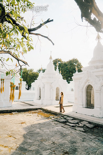 Young Caucasian woman walking in Kuthodaw Pagoda in Mandalay at sunrise, Myanmar - gettyimageskorea