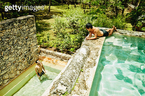 Male friends in discussion while relaxing in pools at luxury tropical resort - gettyimageskorea