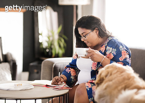 Shot of an attractive woman writing in her diary while sitting in living room with a cup of coffee - gettyimageskorea