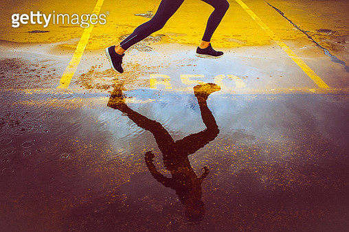 Young person running over the yellow parking lot. Black sport clothing - sport shoes, running tights, and a jacket. High angle view of a runner's legs and its reflection in the water. - gettyimageskorea