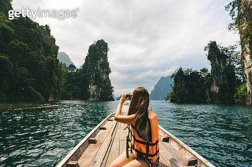 Female tourist exploring lush Jungle lake surrounded by limestone cliffs, Khao Sok National Park, Thailand - gettyimageskorea