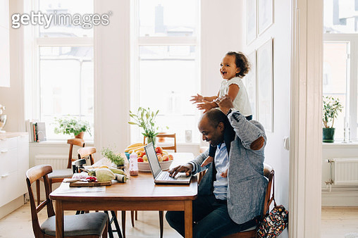 Father carrying cheerful daughter on shoulder while working on laptop at table in house - gettyimageskorea