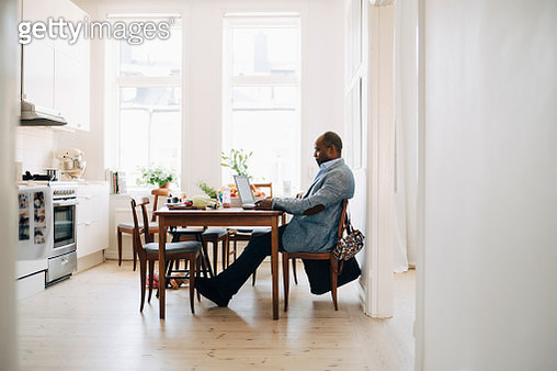 Full length of mature man working on laptop while sitting in kitchen at home - gettyimageskorea