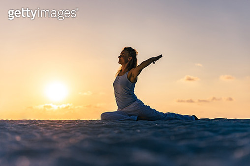Smiling woman doing Yoga exercises with her arms outstretched on the beach at sunrise. Copy space. - gettyimageskorea