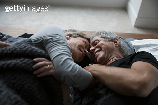 Affectionate, romantic senior couple cuddling in bed - gettyimageskorea