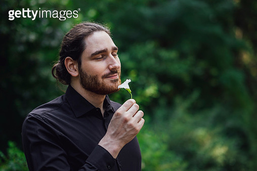 Young man, dressed in black, standing in park, smelling flower - gettyimageskorea