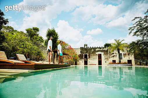 Male friends standing at edge of pool at luxury tropical resort - gettyimageskorea