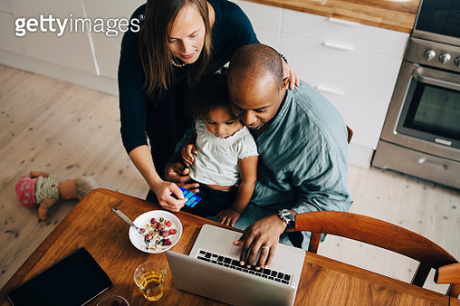 High angle view of parents with daughter shopping online on laptop at dining room - gettyimageskorea