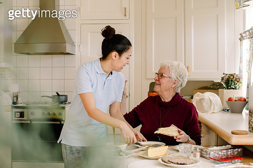 Smiling retired elderly woman talking with female caregiver in kitchen at nursing home - gettyimageskorea