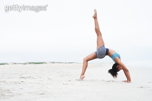 Shot of a young woman doing a handstand at the beach - gettyimageskorea