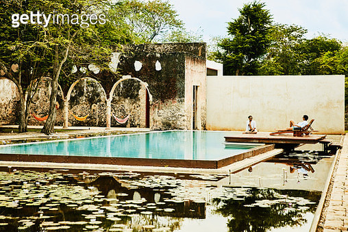 Male friends relaxing by pool in courtyard of luxury tropical resort - gettyimageskorea