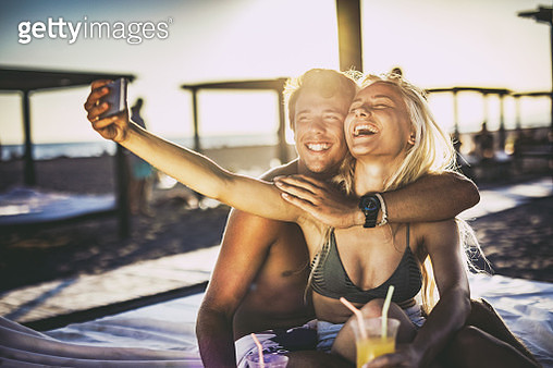 Cheerful couple taking a selfie on a beach at sunset. - gettyimageskorea