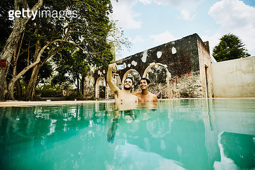 Smiling gay couple taking selfie with smartphone while relaxing in pool at tropical resort - gettyimageskorea