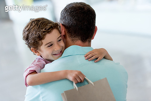 Affectionate son hugging his father at the shopping center - gettyimageskorea