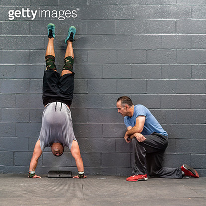 The young Latino athlete doing armstand exercise, emotionally pushing by his coach, the senior 55-years-old Latinx man.The gym in Pennsylvania, USA - gettyimageskorea