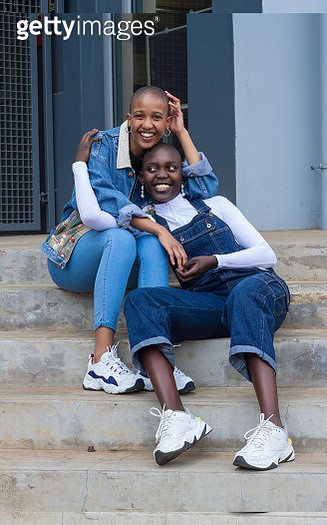Lesbian couple from South Africa cuddling on steps. - gettyimageskorea