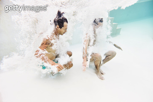 Underwater view of two male friends jumping into pool - gettyimageskorea