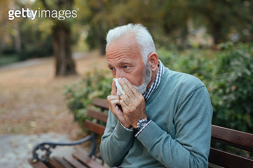 Elderly man with cold blowing his nose in the park - gettyimageskorea