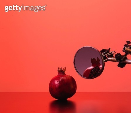 Pomegranate And Mirror Against Red Background - gettyimageskorea