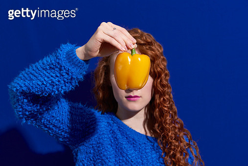 woman holding yellow pepper in front of face - gettyimageskorea