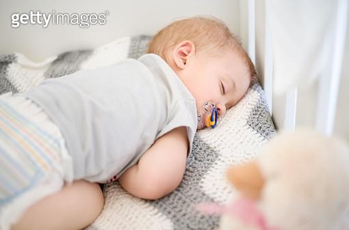 Newborn baby sleeping peacefully in crib. - gettyimageskorea