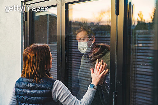 Woman looking at masked husband quarantined behind window - gettyimageskorea