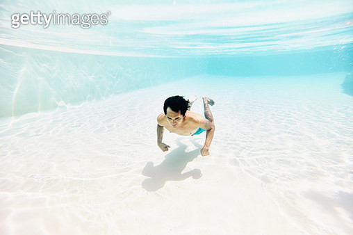 Underwater view of man swimming underwater in pool - gettyimageskorea