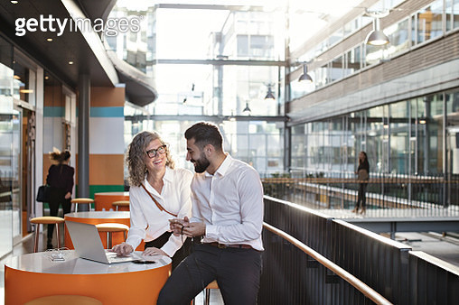 Smiling business colleagues discussing over laptop at atrium - gettyimageskorea