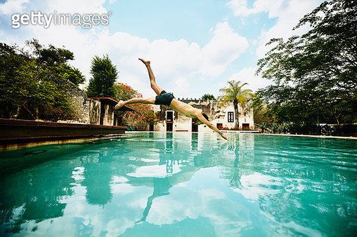 Man diving into pool at luxury tropical resort - gettyimageskorea