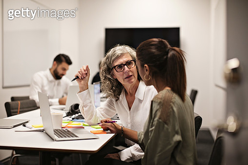 Businesswomen discussing over laptop while male colleague working in background - gettyimageskorea