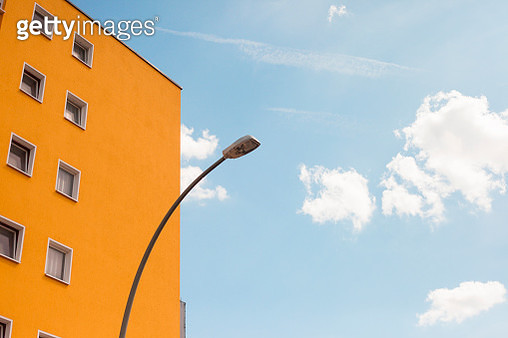 Orange building facade and lamppost on a blue sky backdrop - gettyimageskorea