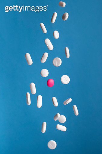 Falling white pills with one pink pill in mid air.. - gettyimageskorea